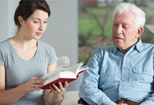 Woman reading to elderly man.