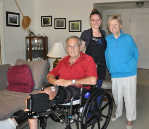 Man in wheelchair with wife smiling with caregiver