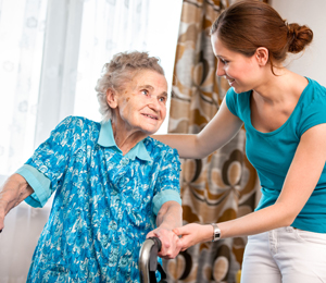 Caregiver helping elderly woman with walker