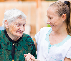 Picture of caregiver and elderly woman holding hands