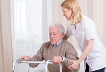 Picture of a caregiver helping an elderly man with his walker