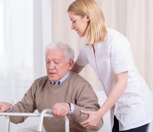 Woman helping elderly man with walker