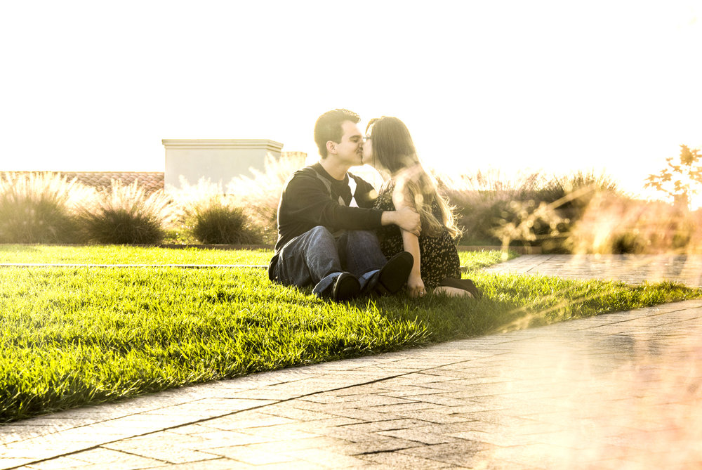 engagement-couple-sitting-grass-kissing.jpg