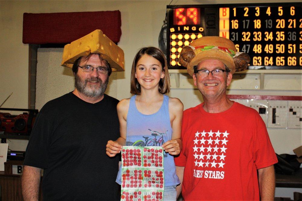 Cal Murphy and Madalyn Leinweber of Ripon stand next to Bingo caller Phil Burkart at the last Brats & Bingo game.