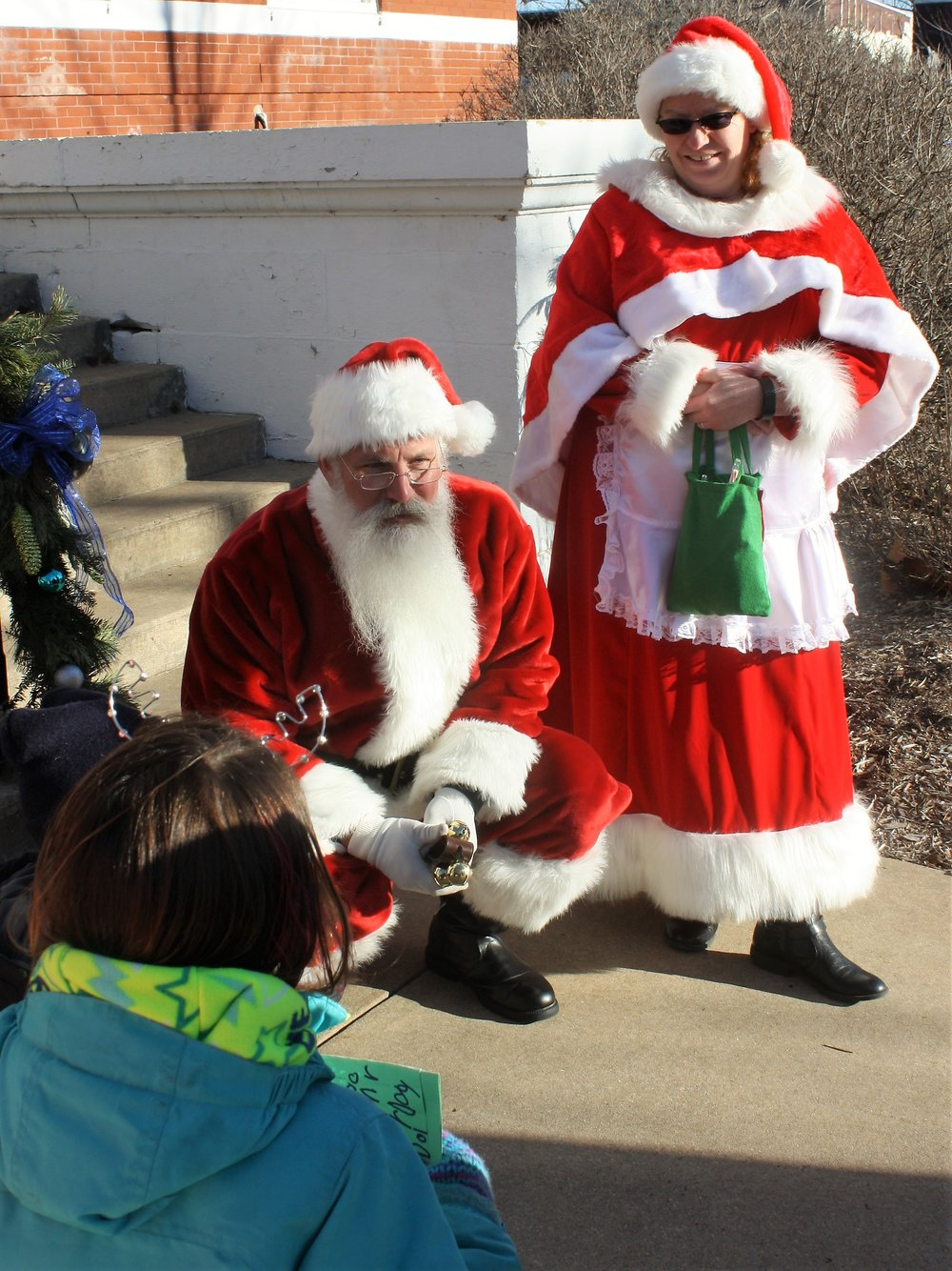 Mr. and Mrs. Claus welcome cookie decorating helpers to Town Square.