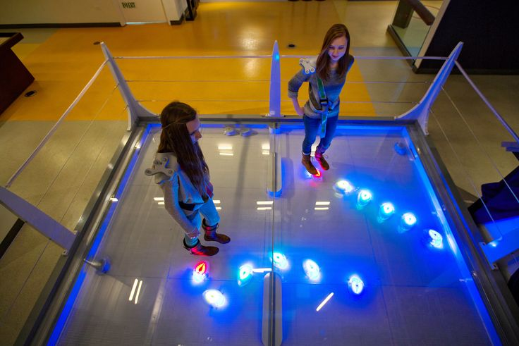 Hannah Lawrence, left, and Rachel Lawrence playing Robot Swarm, an exhibit in which one can control the movement of differently colored robots. Ozier Muhammad / The New York Times