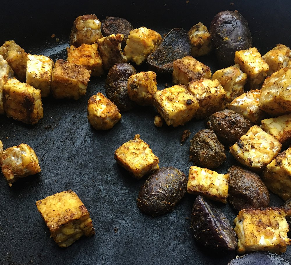 2. Next, throw your potatoes and tempeh into a frying pan and begin to saute with 1 tbl of olive oil. After a minute or two, mix in the spices Old Bay, turmeric, ginger ground, and curry powder. Saute it for a few minutes over medium heat until the potatoes and tempeh begin to get a light brown sear. Set aside.