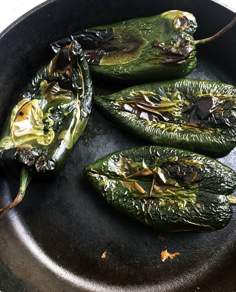 2. Next, place the poblanos in a castiron pan, broil for a few minutes in the oven then switch to pan and cook on high heat. You want to burn the poblanos until the skin starts to crack and peel off. It should take another 6-8 minutes.