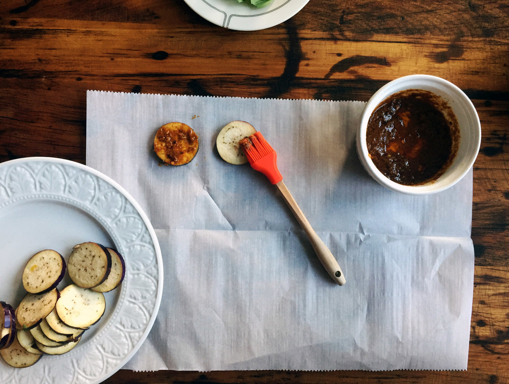 3. While those cook, mix your marinade in a small bowl, place parchment paper on surface and marinate both sides of each eggplant piece.