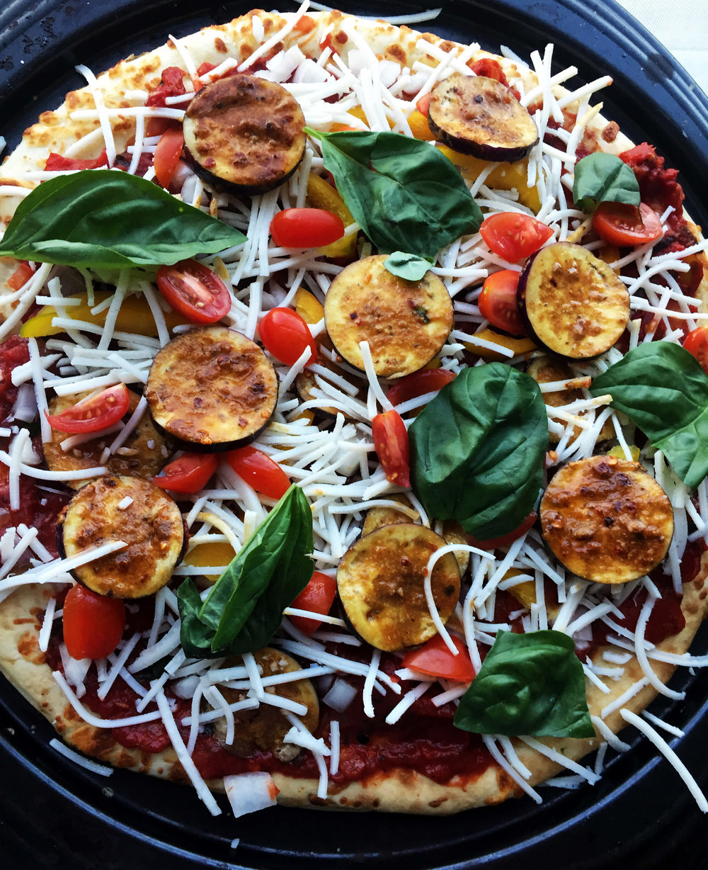 8. Add the cheese, pepperoni slices, a few grape tomatoes, and basil pieces.