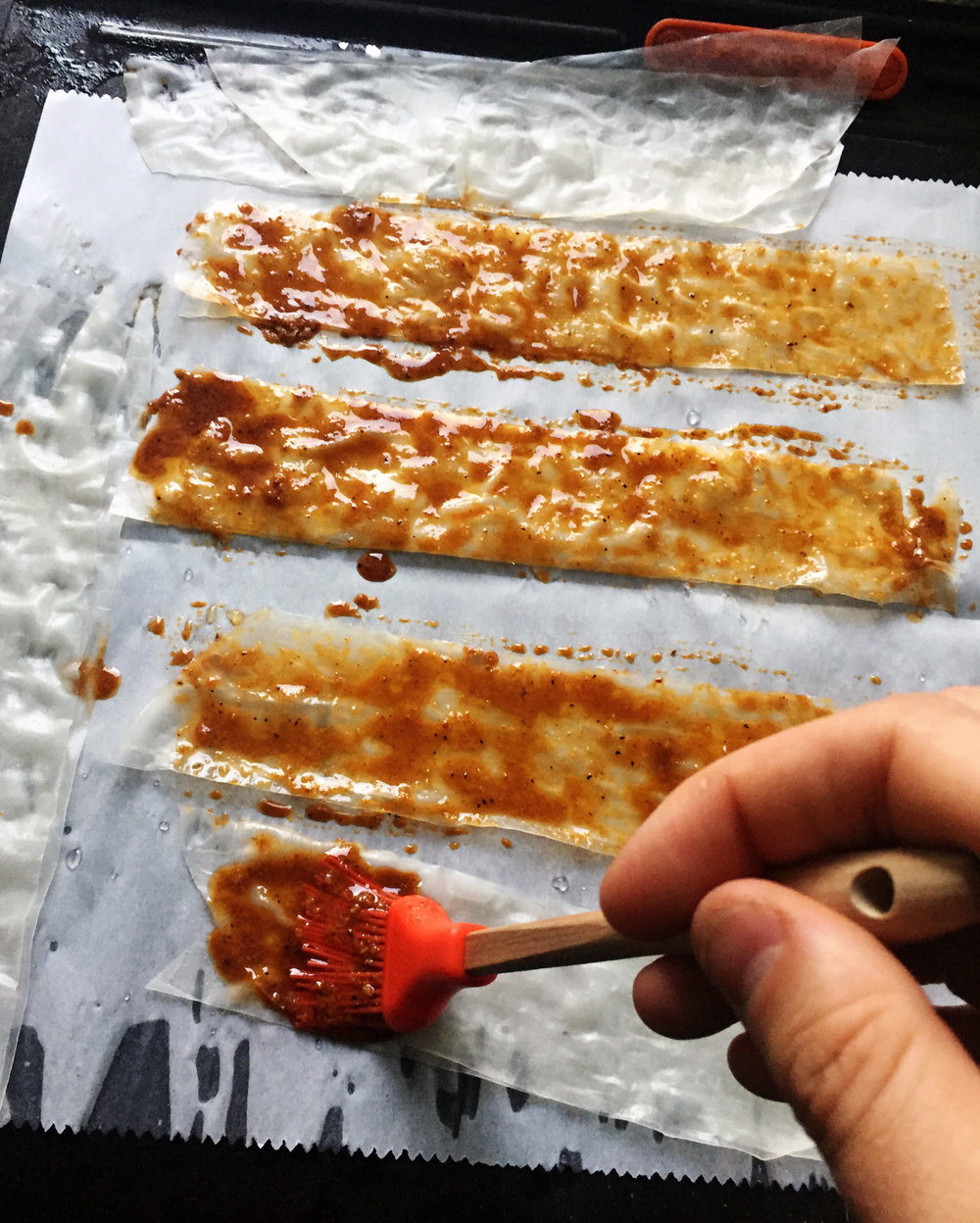5. Using a pastry brush, slap on the marinade onto each strip. Coat well. Flip over the strips and add the marinade to the other side. Place the pans of bacon into the oven and bake at 400F for 8-9 minutes. At 6-7 minutes check it to make sure it is not burned. I keep a close eye as it can burn quickly.