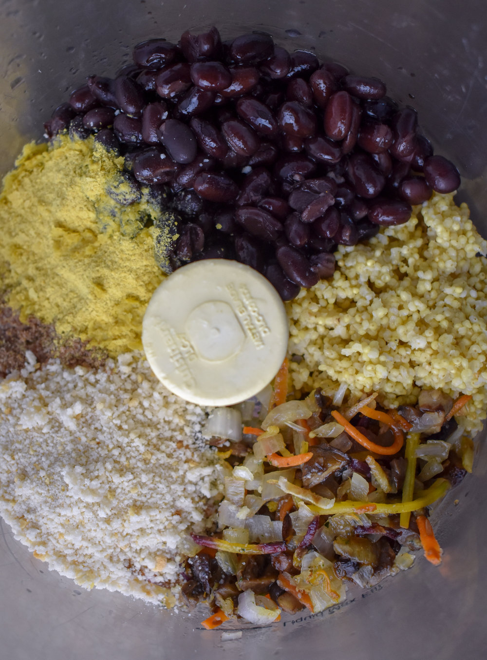 2. Place millet, black beans, mushroom mixture, breadcrumbs, nutritional yeast, spices, flaxmeal, aminos, and lemon juice into food processor. Pulse until well mixed roughly 9-10 times. The mixture should stick together very easily and leave just a tiny bit of residue on your hands.