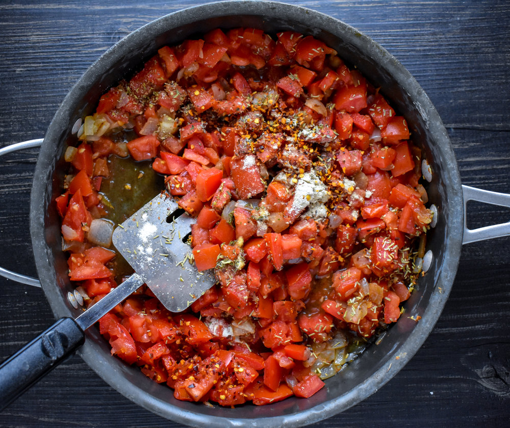 1. To start, cook the shallots and garlic from tomato sauce in a large deep pan with oil over medium heat for 4 minutes. Add tomatoes, spices, tomato paste, and cook over medium low heat for 15 minutes. Add basil and cook another 10 minutes. The sauce will start to break down.