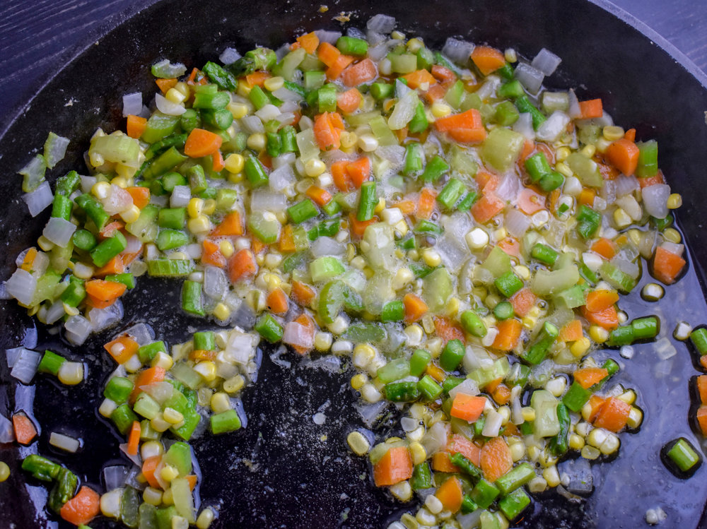 4. Next, add the corn, asparagus, celery, and carrots to the same pan with the onions. Cook for another 2-3 minutes.