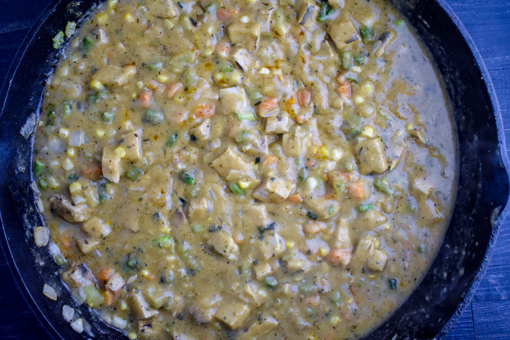 5. Next, add the flour + spices to the mixture. Coat the veggies well in it and then add the milk and vegetable broth. Stir it around for 20-30 seconds. It should be thickening. Finally, add in the chicken pieces you had set aside from before. Turn the heat off the pan and mix it all together.