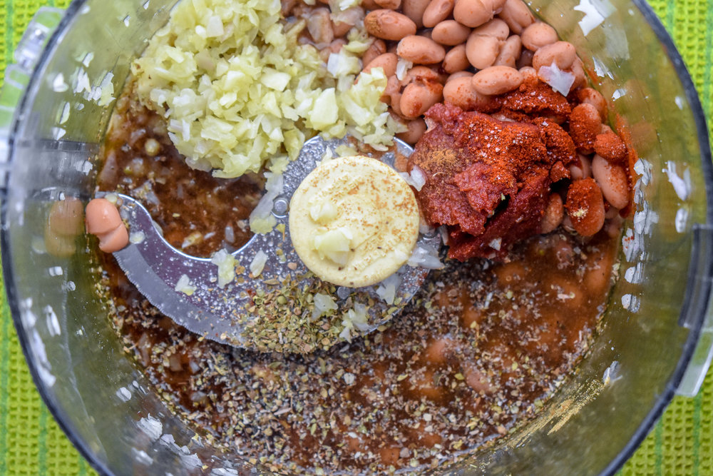 2. Add onions + garlic to food processor  or high-speed blender along with beans, water, coconut aminos, tomato paste, and spices. Mix until it creates a smooth paste.