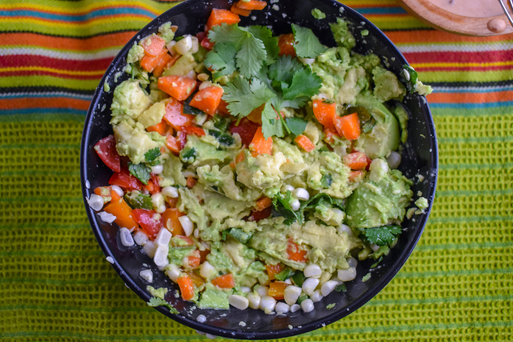 8. With 15 minutes left of steaming, make the guacamole. Add lime juice + salt to bottom of medium bowl. Add in all the chopped ingredients sans avocado. Mix well with a spoon. Add in avocado then mix with a fork + spoon to break up the avocado and mix in but keep it chunky.