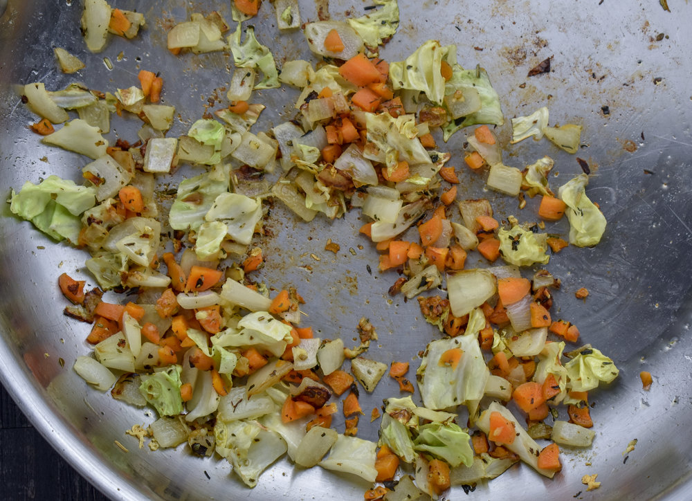 6. As the seitan continues to bake, we will work on the rest of the spring roll filling. Add oil, onions, garlic, and cabbage to a large frying pan. Cook over medium heat for 3-4 minutes, add carrots and continue to cook for another 3-4 minutes.  At this point, mix together the chia meal and water, set aside.