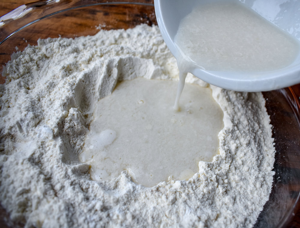 6. Slowly pour in the buttermilk mixture. Begin to slowly stir with a wooden spoon or soft spatula until the mixture is formed into a wet batter.