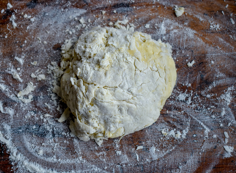 8. Form the biscuit mixture into a ball and place on a flour lined surface. Flip the mixture 2-3 times on the surface and let it rest for a few minutes.
