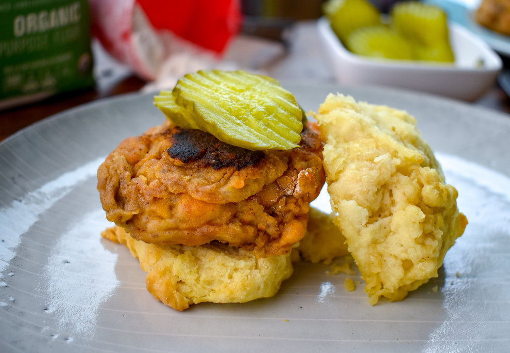 13. Take your biscuits out of the oven and place one biscuit down, layer the chicken on top of it, add a couple pickle chips, and add another biscuit onto the top. Voila!!!