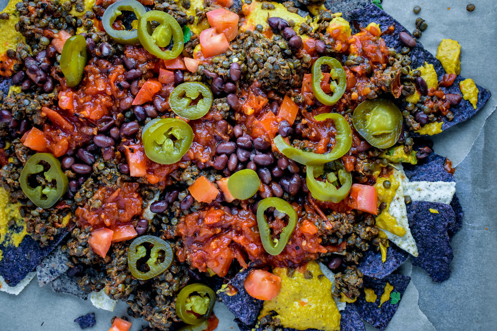 6. Next, add lentil taco meat, black beans, tomatoes, jalapenos, and salsa. Place into the oven and bake for 12 minutes until the cheese starts to brown.