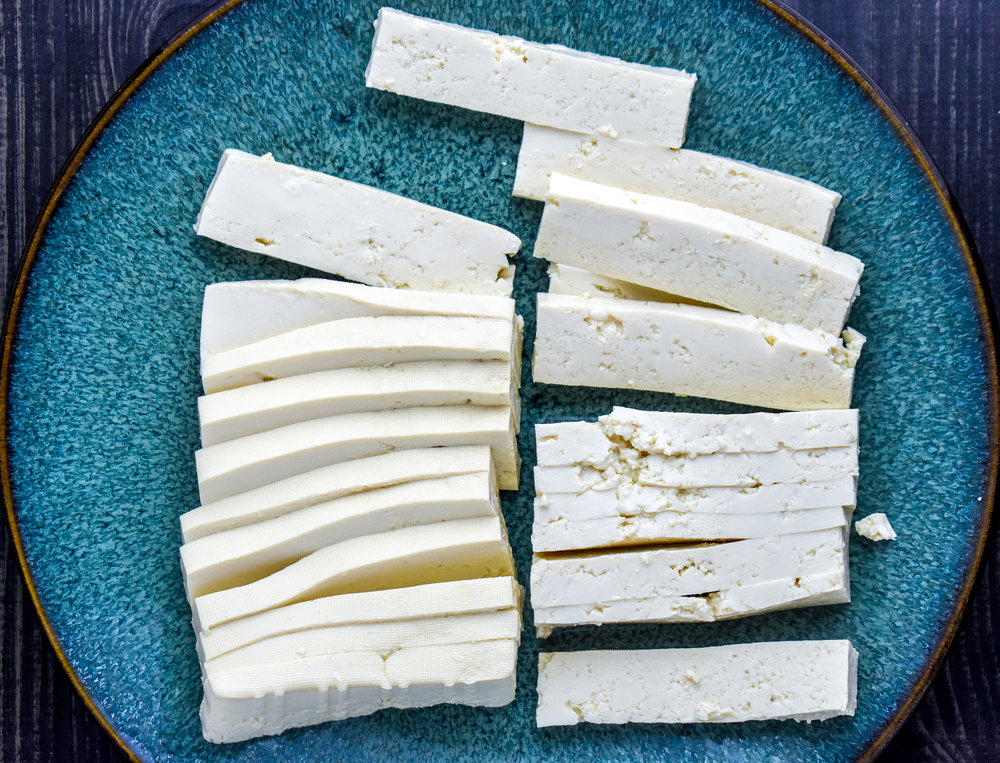 1. To start, chop your tofu into thin long strips. I do this by cutting the tofu in 1/2 across the width and then down the middle. Then I slice it across to create about 16 strips.