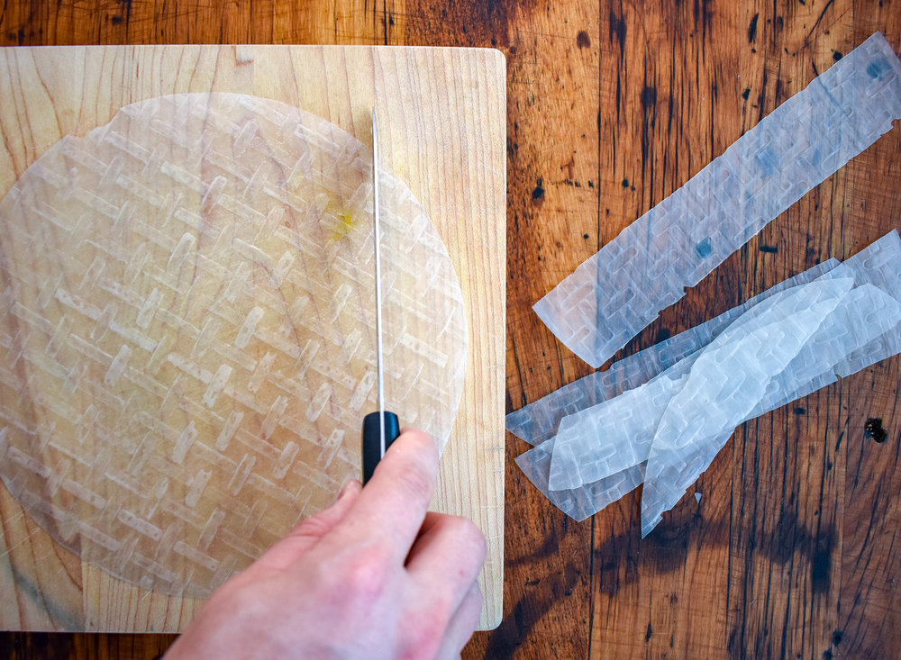 1. To start, place spring roll on cutting board, and slice each sheet into 5 equal width pieces. I use a very sharp knife. If the sheet is cracking on the edges flip it over...usually one side is easier to cut. Apply a good amount of pressure and use a very sharp knife.