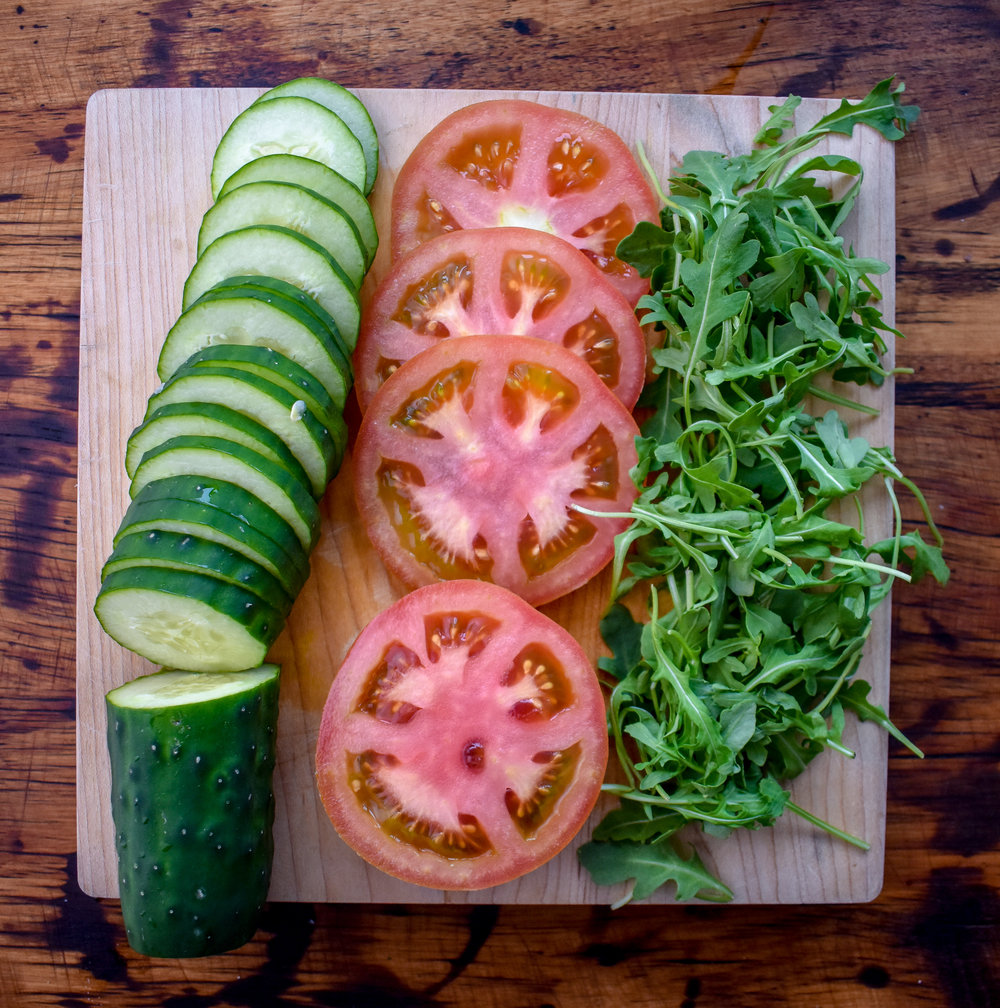 6. Chop cucumbers, tomatoes, and measure out arugula. Mix the avocado with a squeeze of lime and pinch of salt in a seperate bowl.