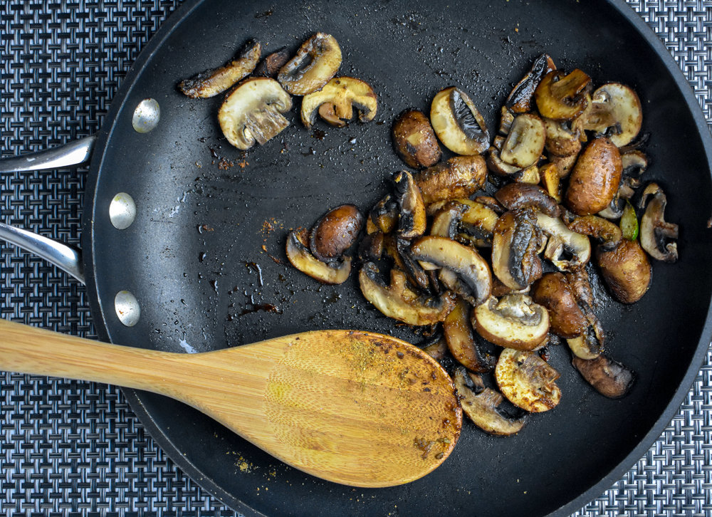 6. While the potatoes are cooking, add olive oil to a medium frying pan over medium-high heat. After warming for 60 seconds, add the mushrooms, liquid aminos, and spices. Cook for a few minutes until softened.