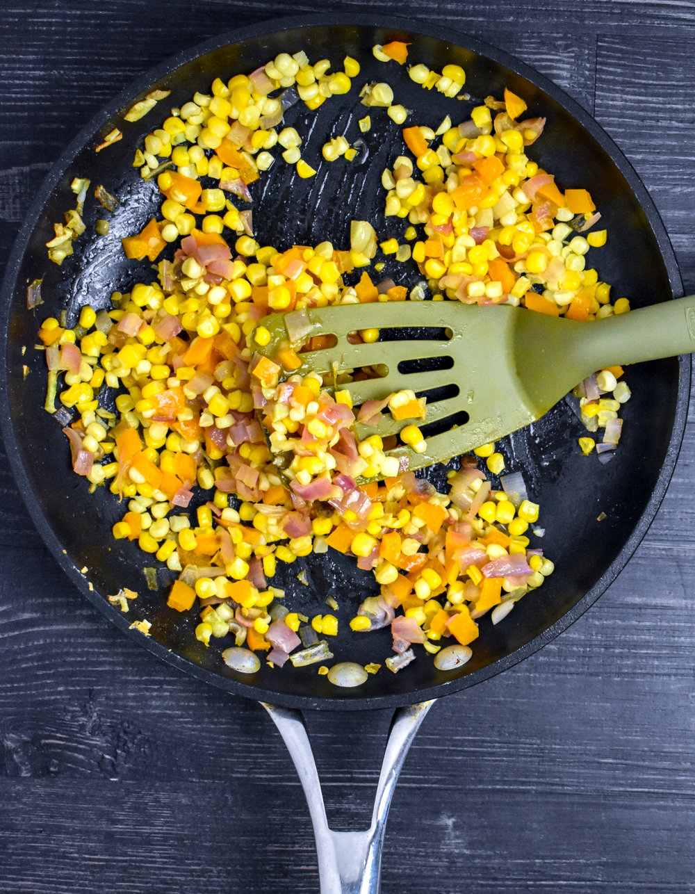 1. Start by adding vegan butter, shallots, and garlic for lime corn to the medium frying pan over medium heat. Cook for 2 minutes. Add in peppers. Cook for 2 minutes. Add in corn, lime juice, and spices. Cook for another 3-4 minutes. Set aside.