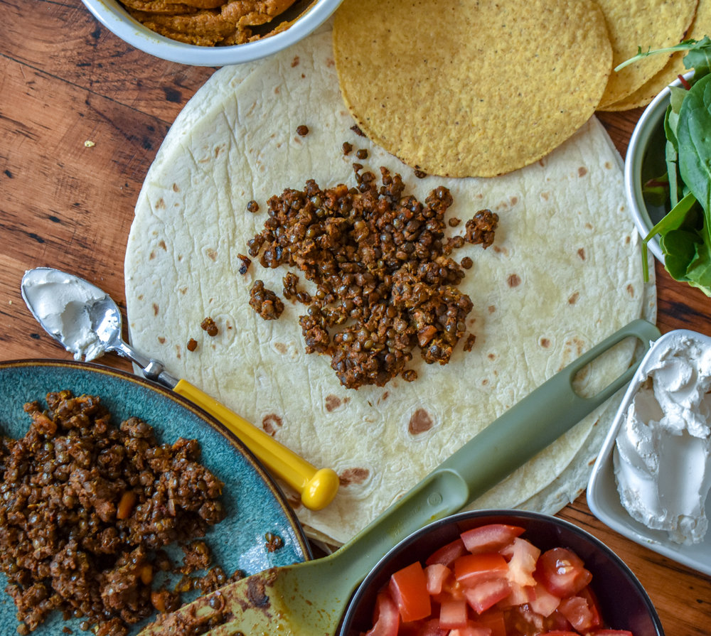 6. Once the lentils are done, set up a station to construct the crunchwrap. Place queso into a small bowl, lentils on a plate or in the pan, and place your sour cream/tomatoes/lettuce into various small bowls.