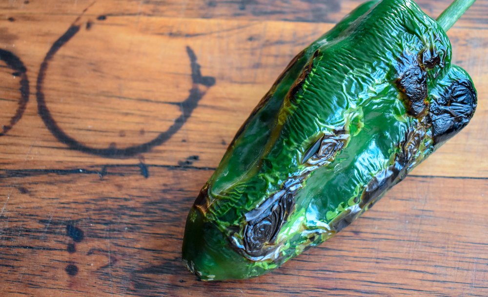 4. While that is cooking, place a poblano ion the stove top or on a dry pan over the stop top and char each side for 60-90 seconds.