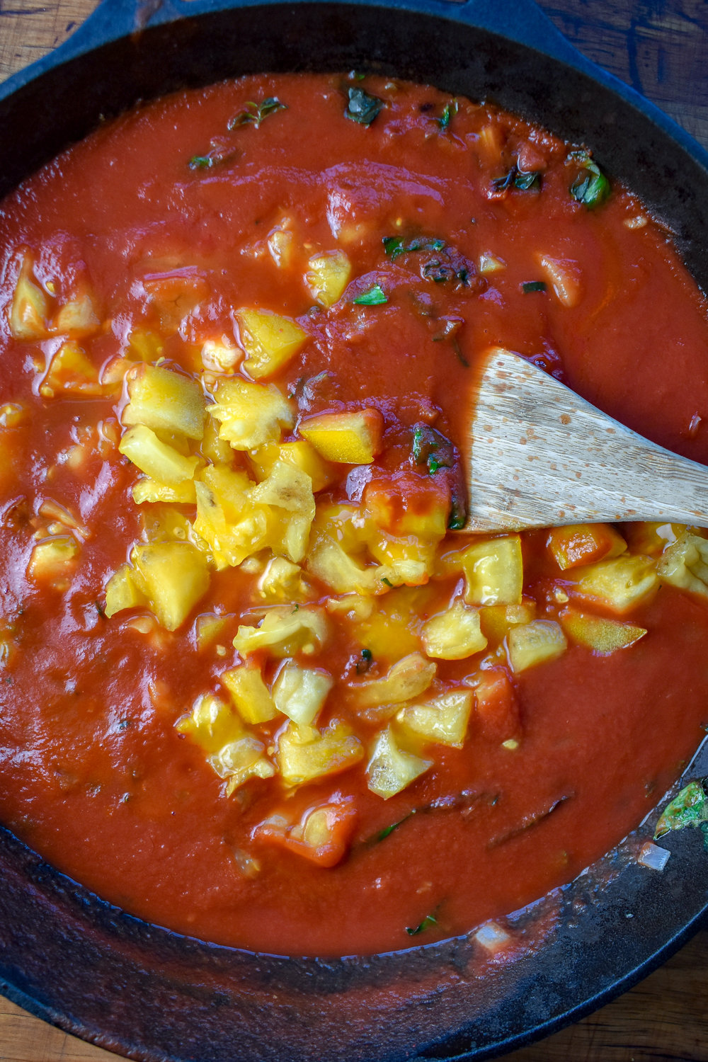 3. Next for the sauce, pour in tomato sauce, add diced tomato, and tomato paste. Reduce heat to low and let simmer. We'll let this simmer till we're done with the rest of the recipe.