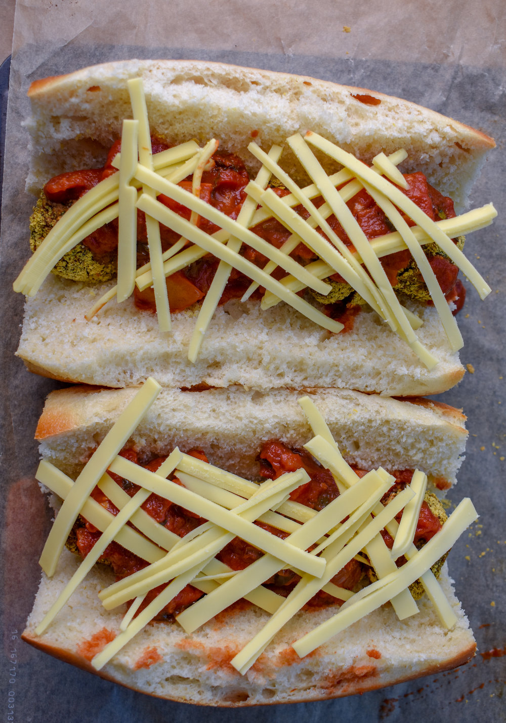 9. Slice your vegan provolone into thin strips and lattice across the top to form a nice cheesy layer. Put back into the oven on broil 525F on the parchment-lined baking pan. Broil for 5 minutes.
