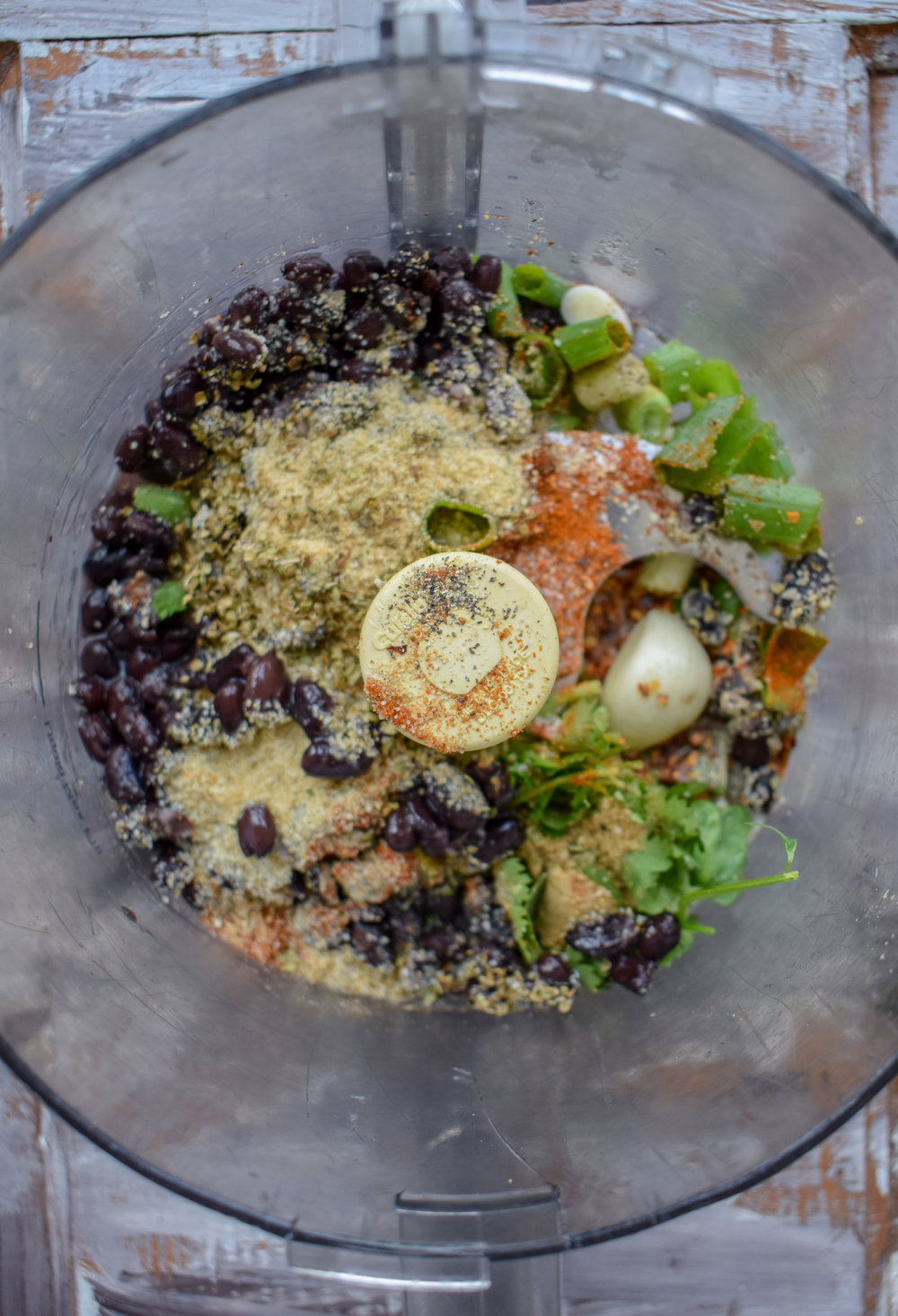 4. While the potatoes/carrot cook, add all the black bean cake ingredients to the food processor or high speed blender. Pulse 15-20 times till blended. Do not turn on and blend straight as it will make it too paste-like.