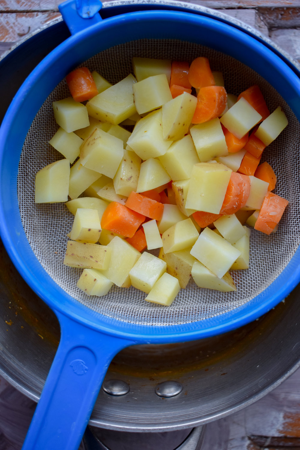 3. Place the potatoes and carrots into a small pot with water that covers them. Turn on high heat, bring to boil, and boil for 10 minutes. Drain when done and set aside.