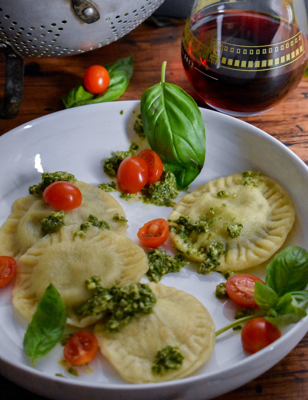 11. Finally, place the ravioli in a boiling pot of water for 3 minutes. Drain. Serve warm with pesto and grape tomatoes over top. Enjoy!