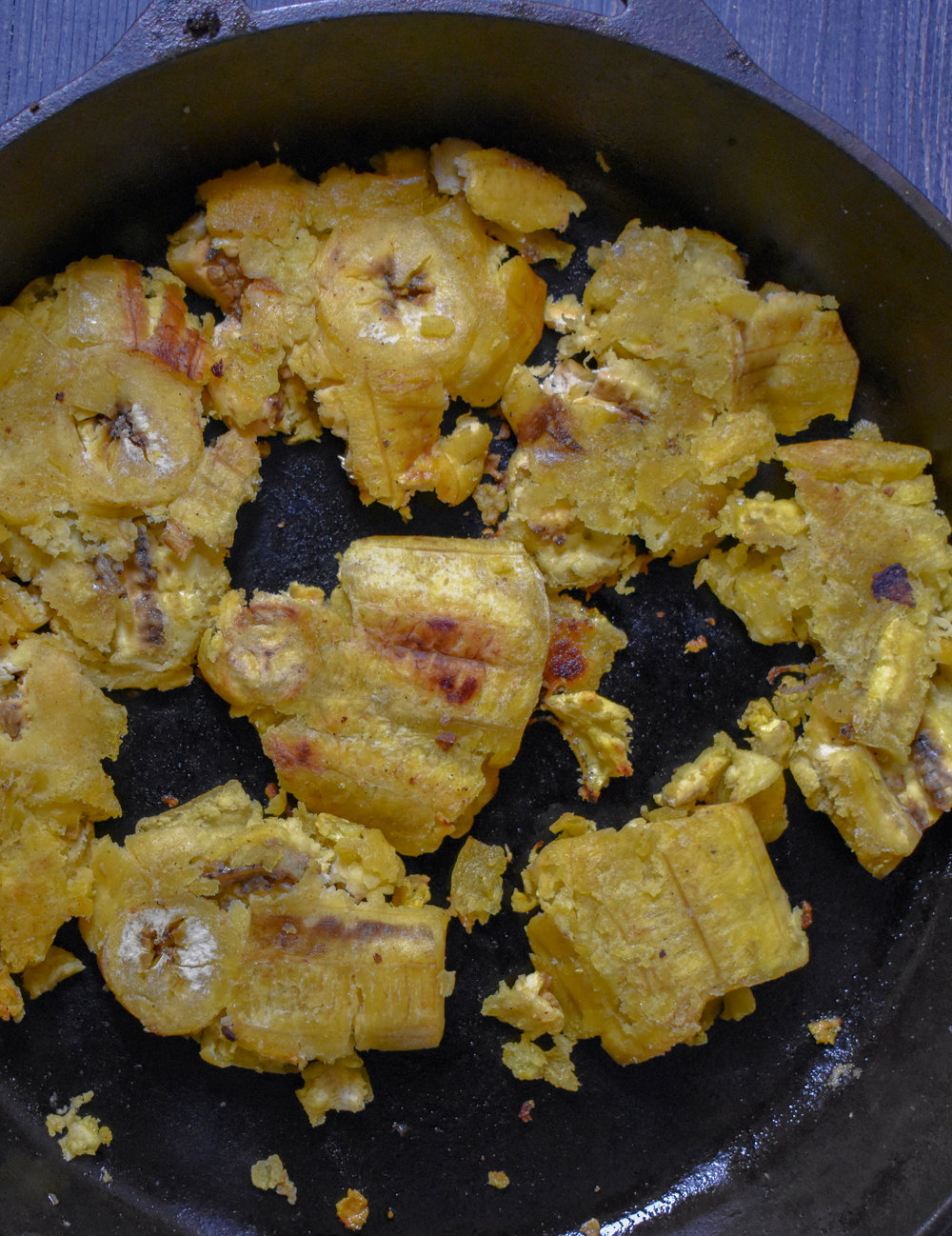 7. With the plantains, use a glass or spatula to smash them down. Take the smashed pieces and throw back into a pan and cook for 1-2 minutes on each side to firm them up.