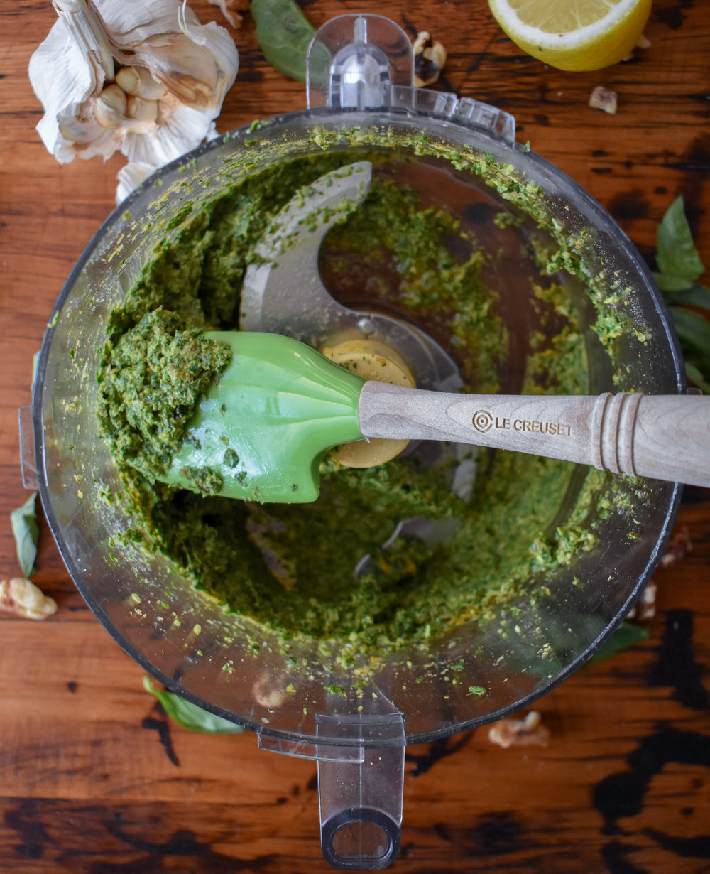 3. Turn the food processor on and drizzle in the olive oil while it blends. Turn off once all oil is in. Scrape down sides and run again for 8-10 seconds until well blended.