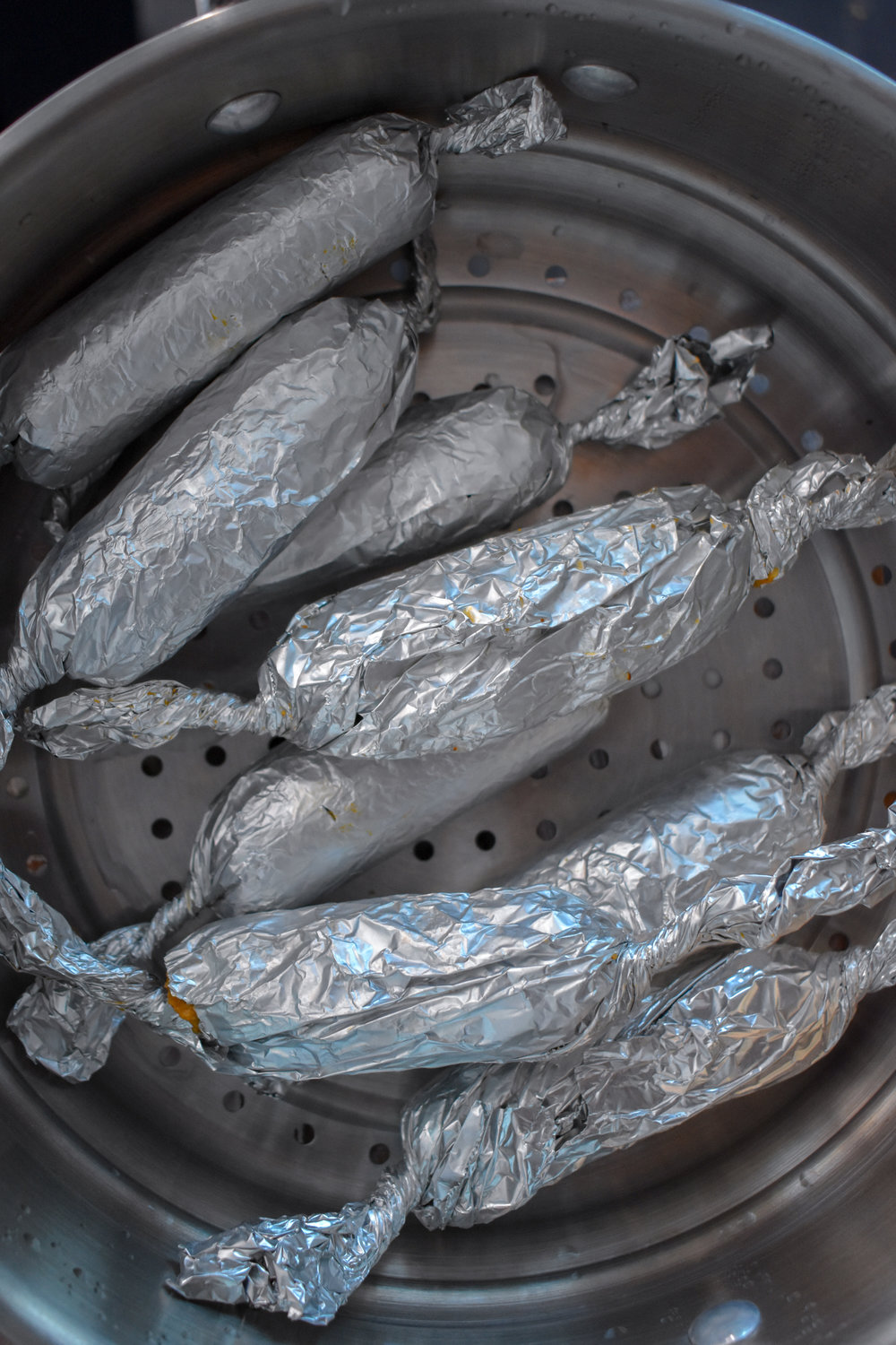 7. Place the rolled up dogs in the top of a steamer pot pan with boiling water underneath and cover. Cook for about 45 minutes.