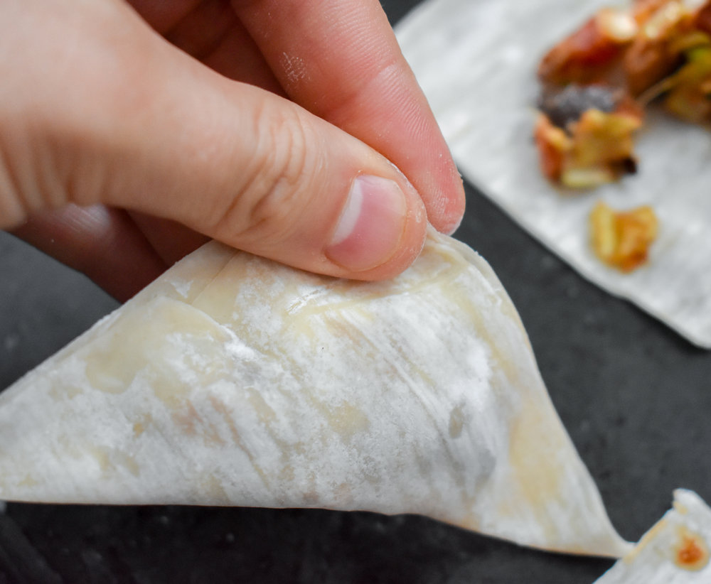 6. To form the wontons, wet your finger and run it along two connected edges of the wrapper. Fold the non-wet edges over so they line up with the wetted edges. Then use your fingers to seal it. If the filling busts, try to use your finger to scoop it in or you have too much!