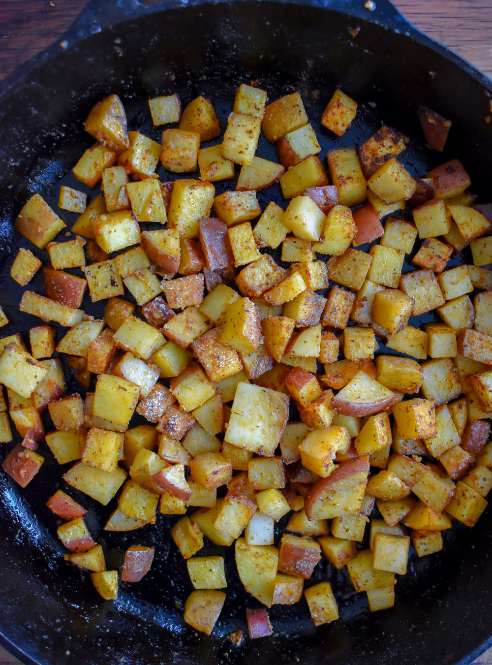 3. Add potatoes to a castiron pan with vegan butter + spices and cook over medium heat for 7-8 minutes until a nice sear forms. Set aside.