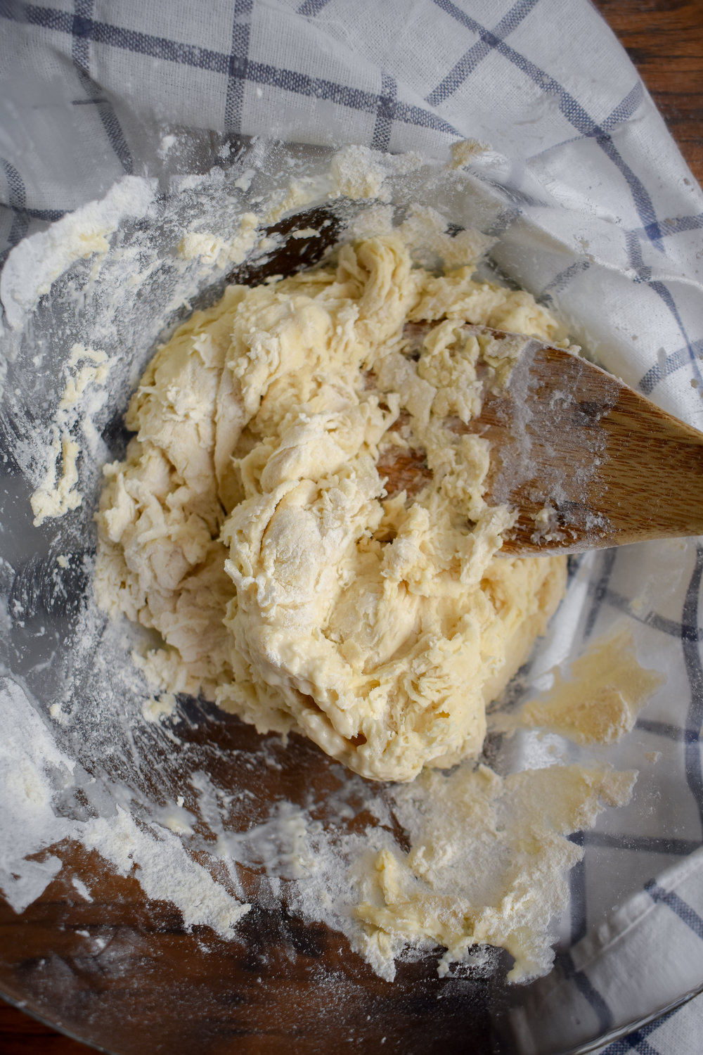 1. To start, add flour + salt from pierogi dough to a bowl. Whisk. In a separate bowl, mix water + melted butter. Slowly pour into flour mixture while stirring with wooden spoon until well mixed.