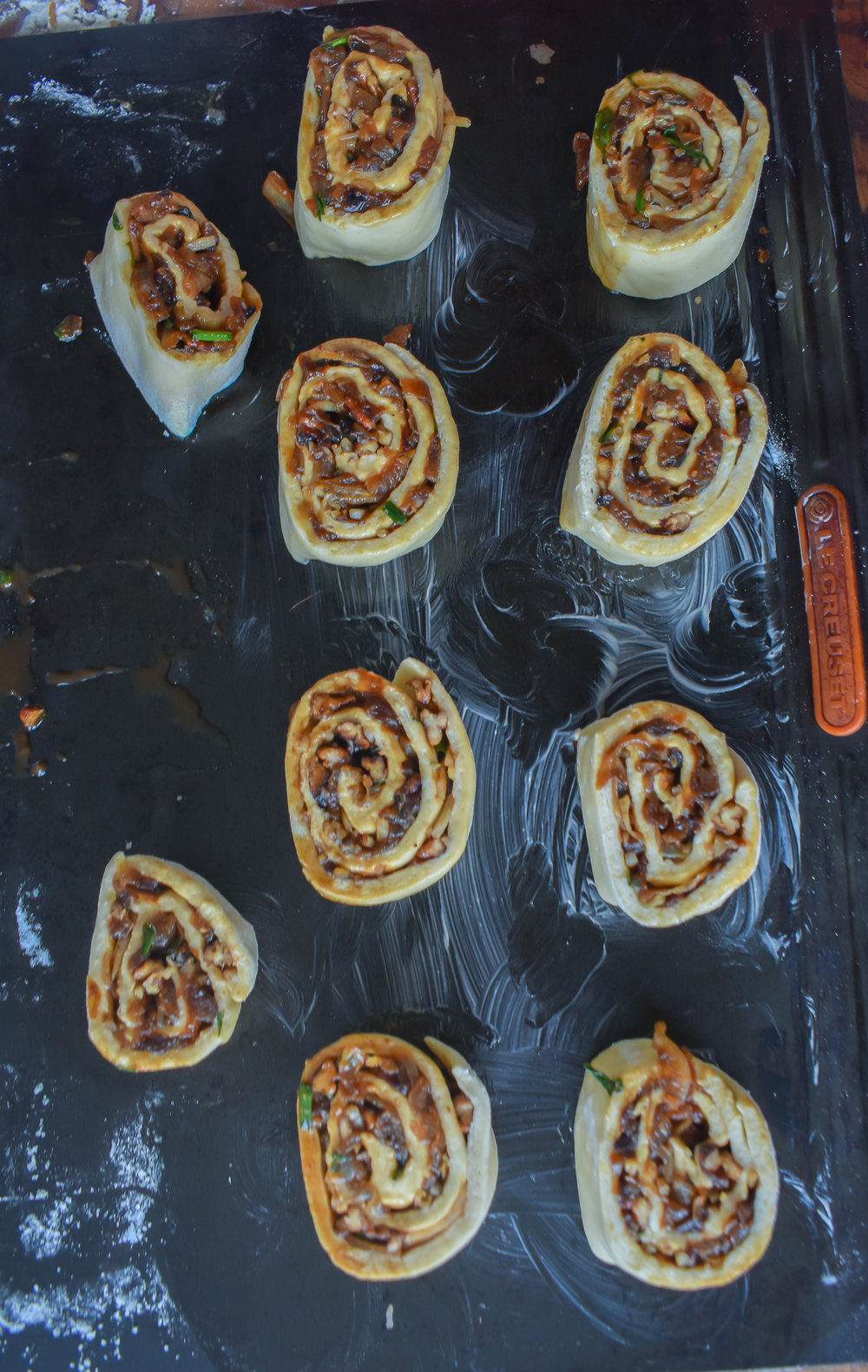 13. Place the rolls on a buttered/oiled baking sheet and add to oven at 375F. Bake for 10 minutes. Pull out and brush down with melted vegan butter with a pastry brush and add a sprinkle of cheese. Bake for another 10 minutes.