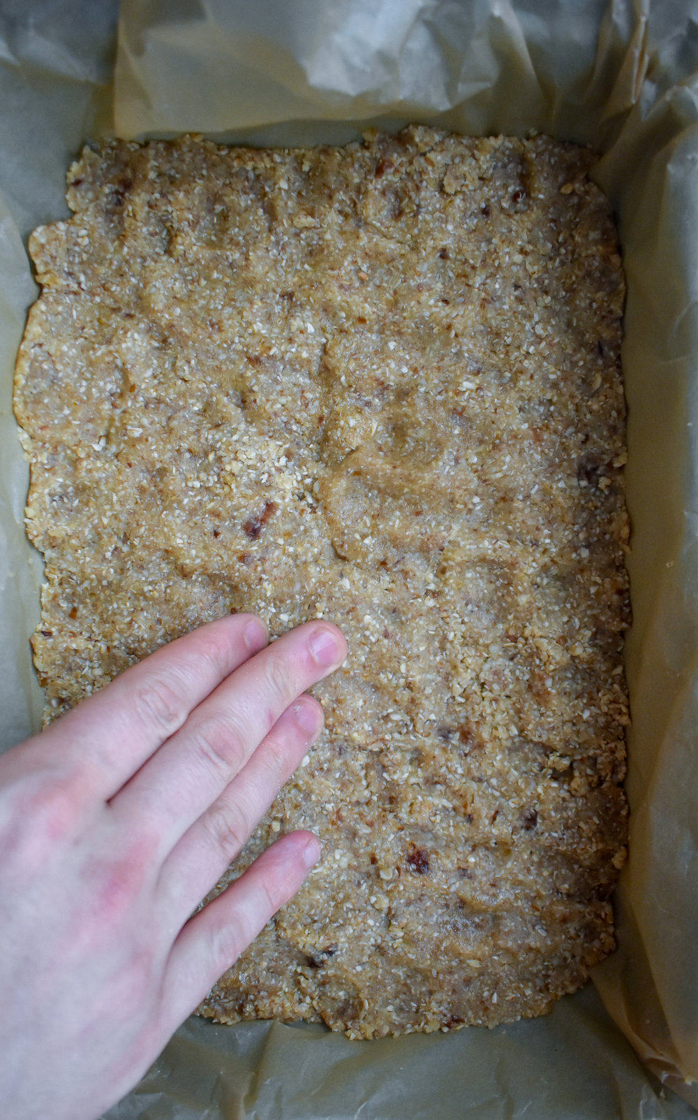 4. Line a 8x14 baking dish with parchment paper. Pour in the crust and press into the dish. Keep an even layer and press into the corners. Place into the oven and bake for 12-14 minutes at 375F.