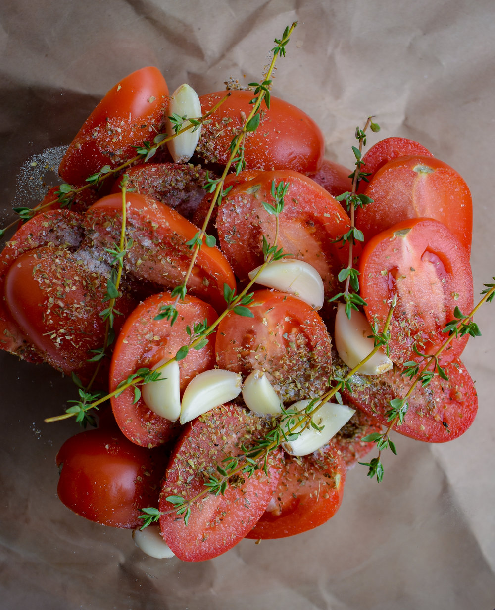 2. Mix with hands roma tomatoes with garlic cloves, sprigs of thyme, olive oil, and sprinkle with salt + pepper.