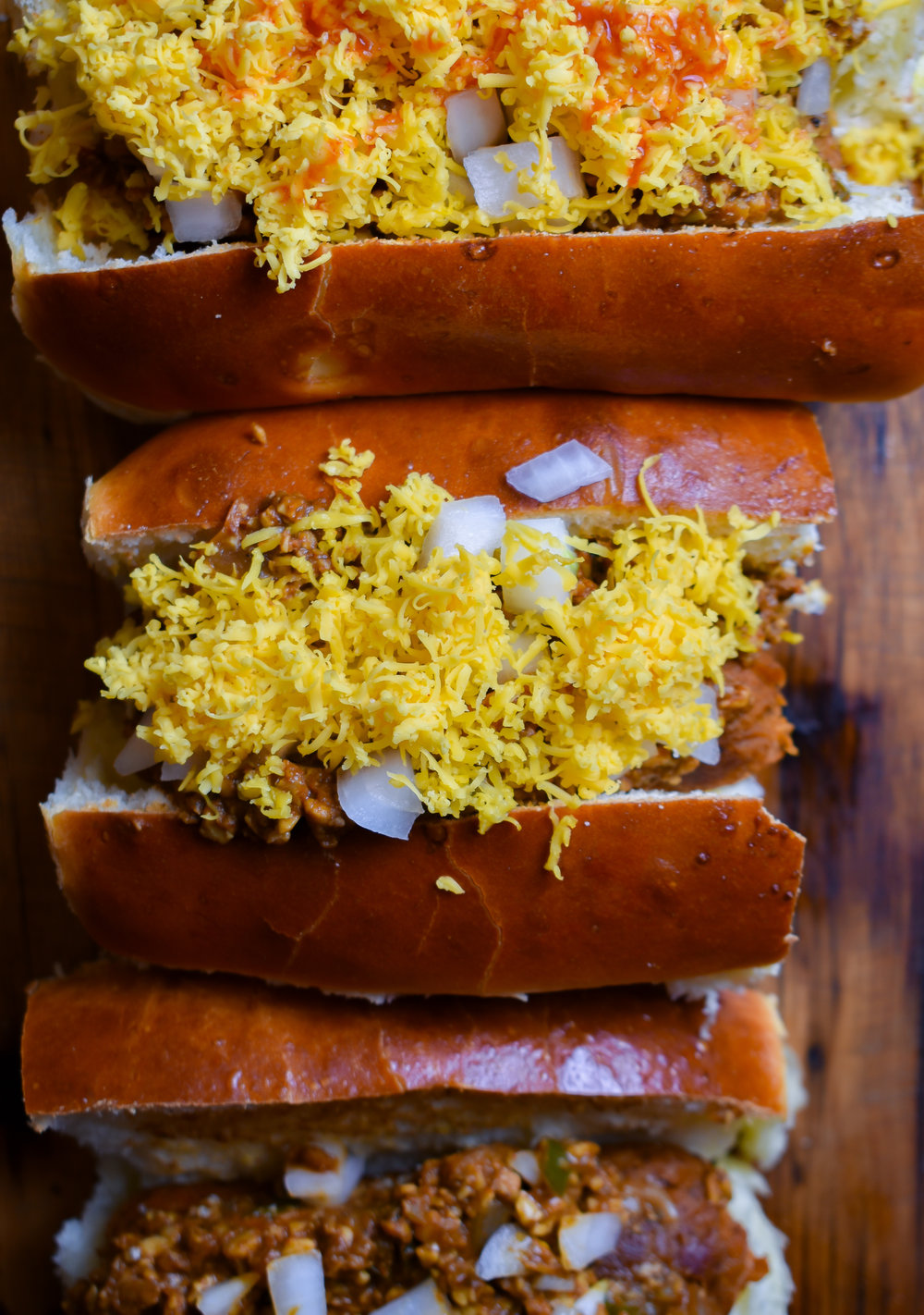 12. To finish, toast your hot dog buns and layer on hot dog, chili, chopped white onions (optional), and cheese. I like to finish mine with some Louisiana hot sauce!