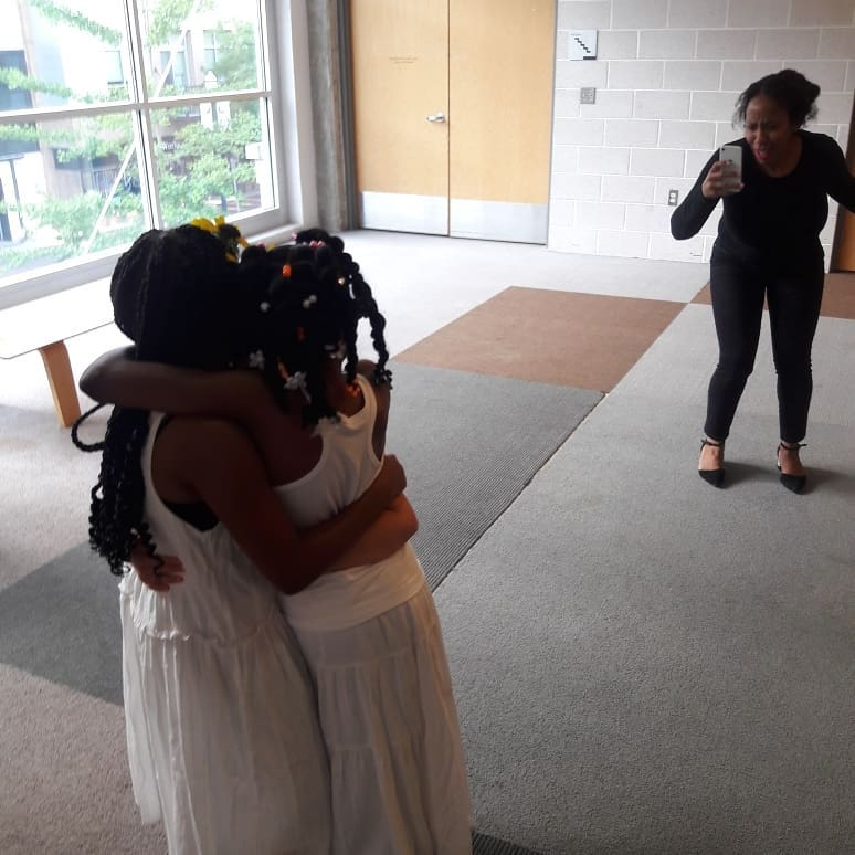 Jazz (ages 7-10) students have a group hug before performing while Ms. Remi looks on