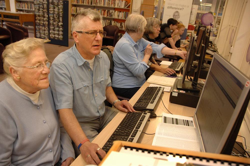 Volunteer Richard Crocker helps Valerie Barron research her family tree
